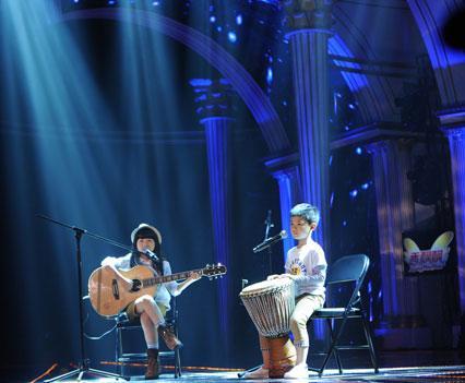 一身小朋克装出场,怀抱与身高不相上下的大木吉他,坐在舞台中央的小